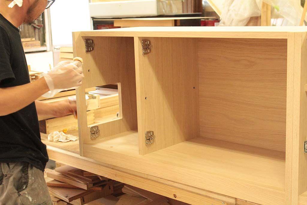 壁のコンセントパネルの位置に合わせて配線穴を開けたテレビボードの側面
