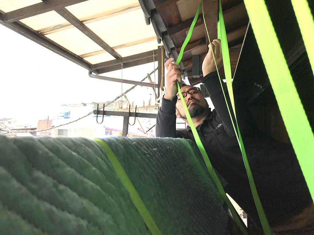 家具を吊り降ろしするためにベルトを庇に巻き付ける