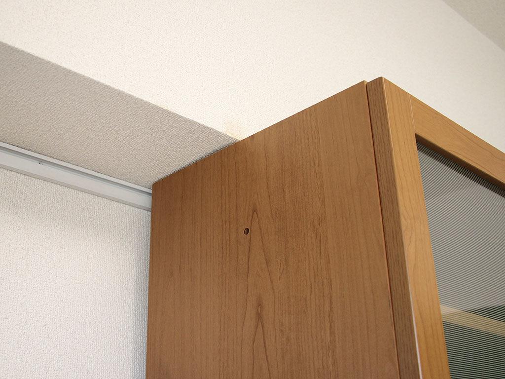 食器棚が天井下に収まり壁面にぴたりと付いている様子