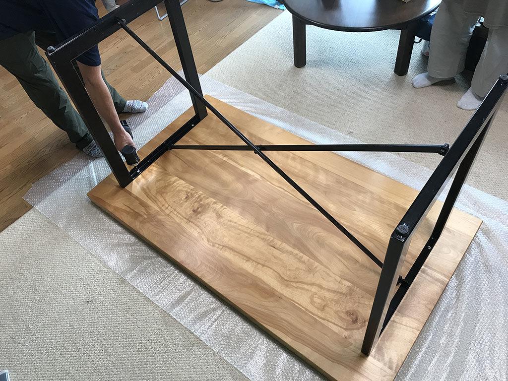 搬出に際してテーブル天板と脚を分解している様子