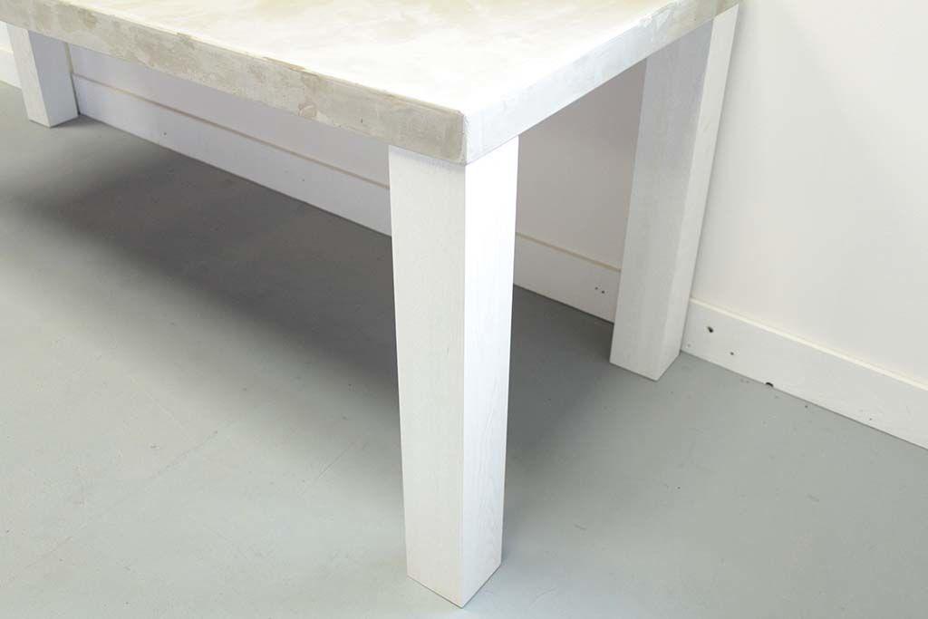 セメント天板に太めの白色木製脚テーブル