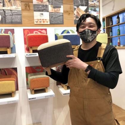ルーツファクトリーの看板商品の『モンペスツール』を持ち笑顔の福井くん