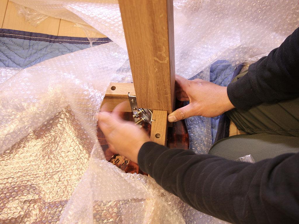 お客様宅にてテーブルの天板と脚を組み立て