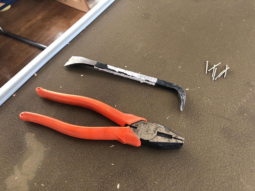 テーブル天板と脚の接合部に使われていた釘を内装バールやペンチで丁寧に引き抜く