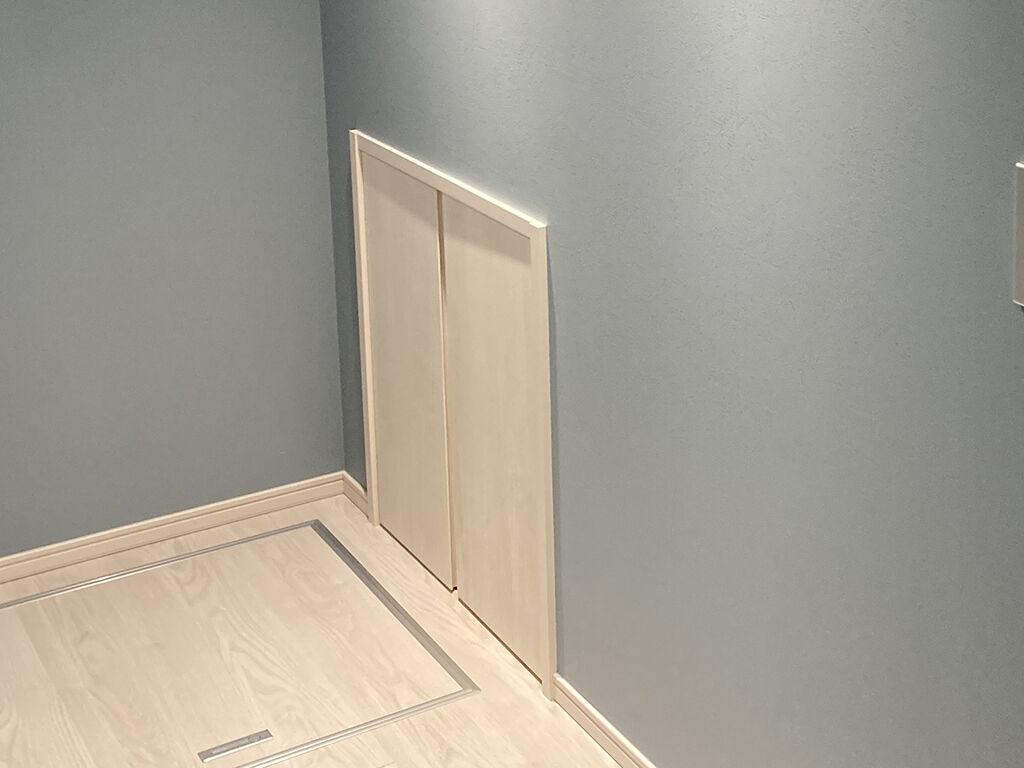 テーブル設置スペースの壁面にある両開き扉の壁面収納
