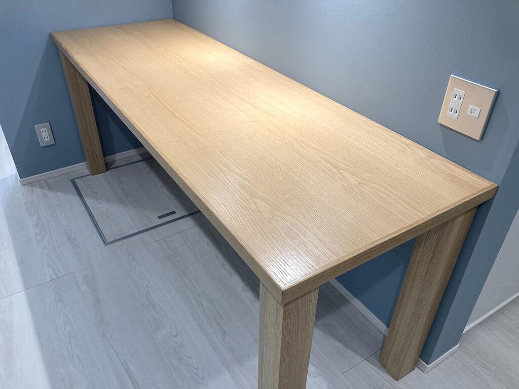 ブルーグレイの壁面に設置したオーク材のダイニングテーブル