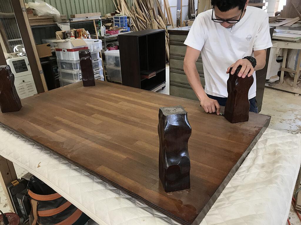 座卓の天板にはめ込んである脚を工具を使いながら丁寧に取り外す