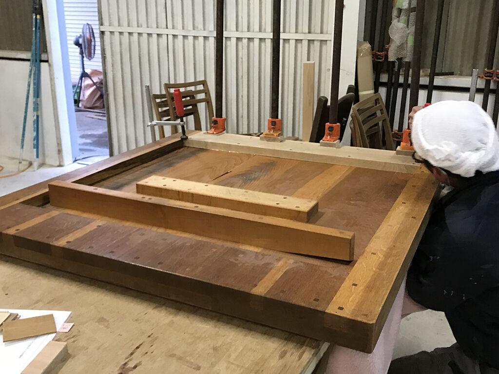 縁のみ材が二重になっていて厚みのあるダイニングテーブルの天板裏